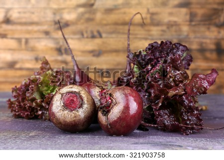 Red beets with lettuce on wooden table close up - stock photo