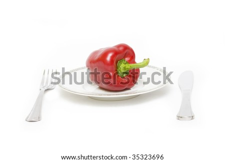 Red bell pepper on plate with fork and knife  isolated on white