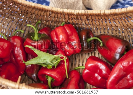 Red bell peppers in a basket on display at a market.