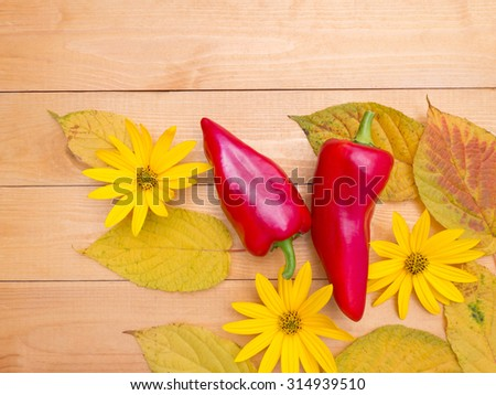 Red bell peppers, yellow topinambour flowers and autumn leaves on the wooden planks background
