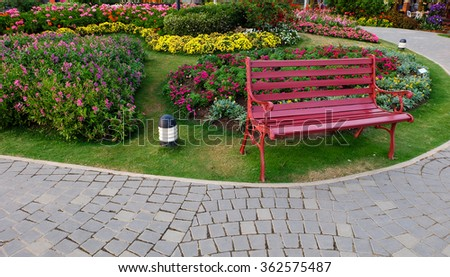 Red bench in a flower garden.