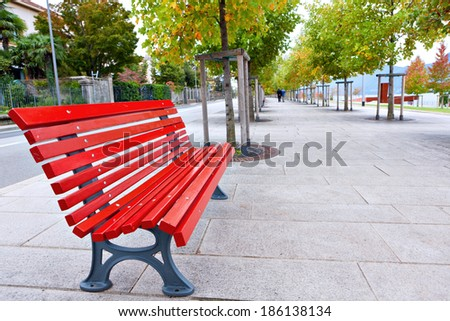 Red bench on neat and clean pedestrian sidewalk in Italy - stock photo