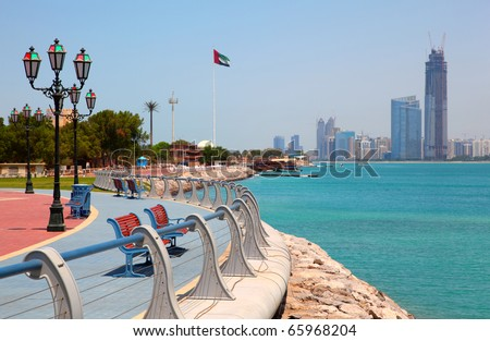 Red benches in park on the seafront against the backdrop of Abu Dhabi buildings - stock photo