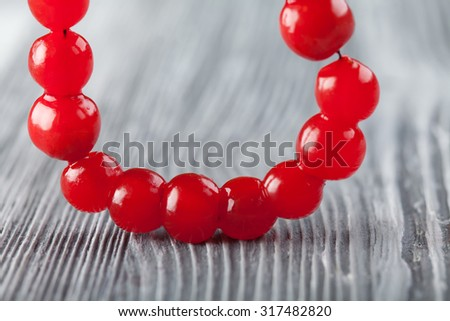 Red berry necklace. Viburnum berries bead, chaplet, beading. Natural, organic small rounded red berry and perforated for threading with others as a necklace. gray background, macro view, soft focus