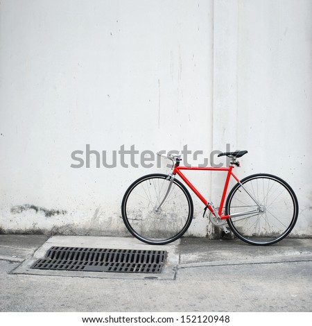 Red bicycle leaning on white wall