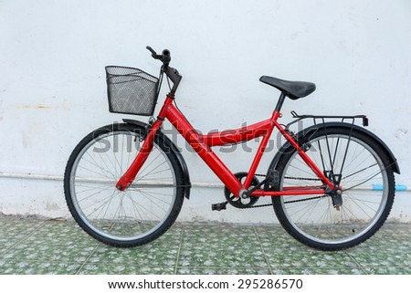 red bicycle on old color  house wall. - stock photo