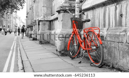 Red Bicycle on the Street, Isolated red color on black and white background, shallow depth of field, blurred walking people, captured in York England