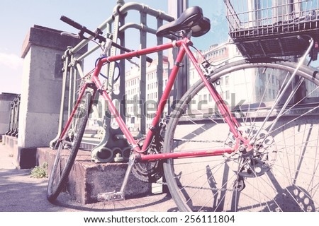 Red bicycle parked in the city (Vienna, Austria) - red bike. Vintage color style - cross processed filtered colors tone. - stock photo