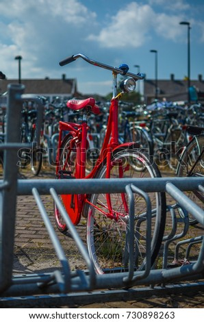 red bike in a bicycle parking rack