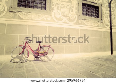red bike leaning against a wall in vintage tone effect - stock photo