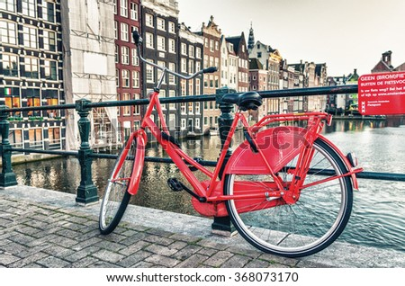 Red bike parked along Amsterdam canal. - stock photo