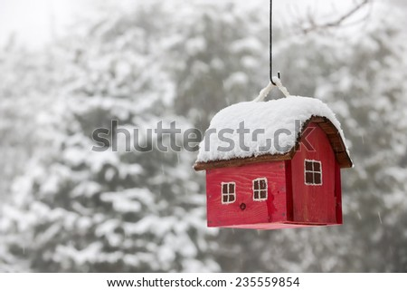 Red bird house hanging outdoors in winter covered with snow - stock photo