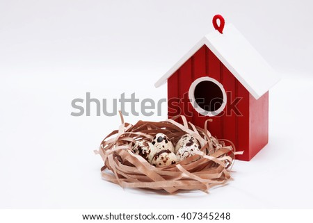 Red birdhouse and decorative nest with quail eggs on a light background  - stock photo