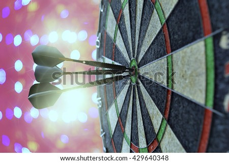 Red, black, and green dartboard on its side with three fiery metal tipped darts in the bulls eye. On pink bokeh as  background.