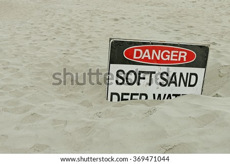 red, black and white Danger, Soft Sand, Deep Water sign - stock photo