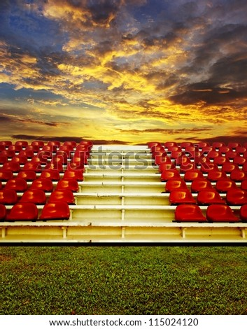 Red bleachers with sunset sky background - stock photo
