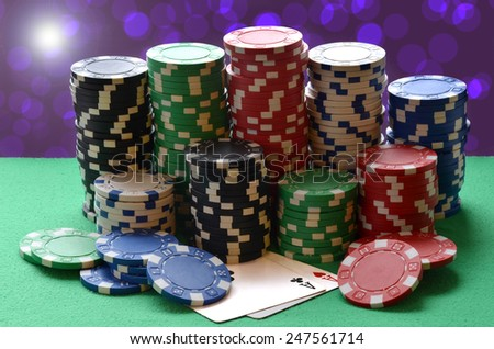 Red, blue, green, white and black poker chips pile and aces on green table