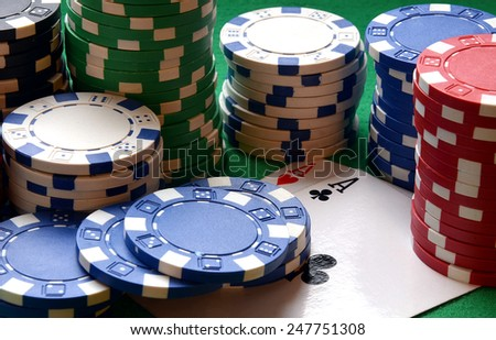 Red, blue, green, white and black poker chips pile and aces on green table - stock photo