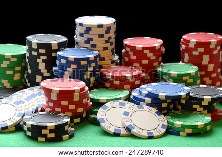 Red, blue, green, white and black poker chips pile on green table - stock photo