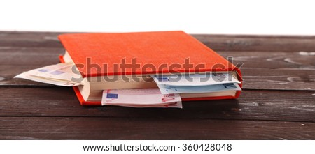Red book with nested euro banknotes on white background. Stash of money - stock photo