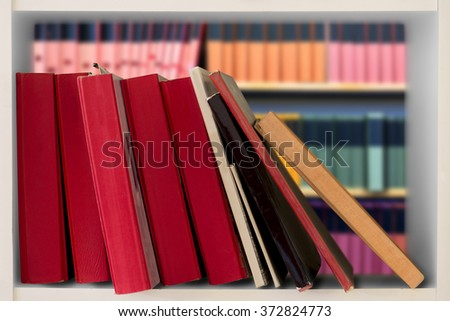 Red books in white bookcase and shelves with archive in background