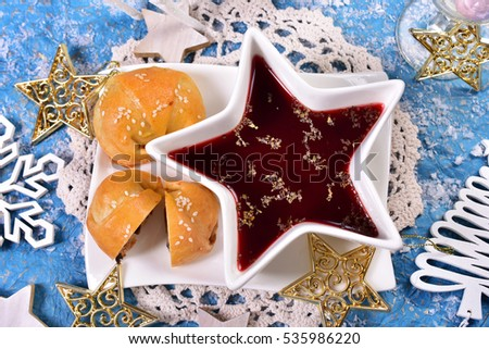 red borscht in white star shaped bowl and mushroom pastries for christmas eve supper