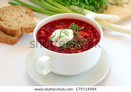 Red borscht soup with dill in white bowl - stock photo