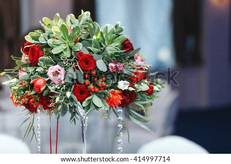 Red bouquet of roses, ranunculus, greenery,  decorated with crystals and ribbon
