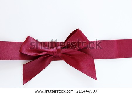 Red bow and ribbon on plain background