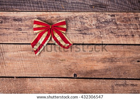 Red bow on a wooden background