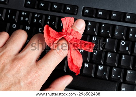 Red bow on finger and computer keyboard - stock photo