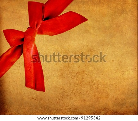 Red bow on grunge paper card - stock photo