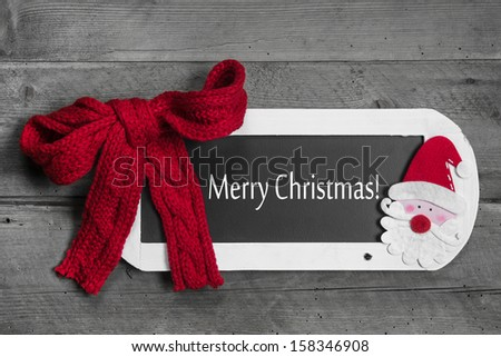 Red bow on menu board with Merry Christmas message on wooden background - stock photo