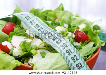 Red bowl with salad on the table in the kitchen with meter to measure waist