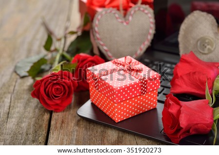 Red box and roses on a wooden background, Valentine's Day concept