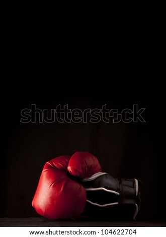 Red boxing glove on black with copy space above - stock photo