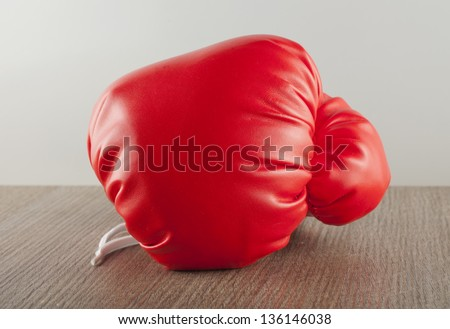 Red Boxing glove over a wooden table