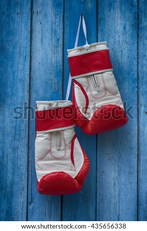 red boxing gloves hanging on the old blue cracked wooden background - stock photo