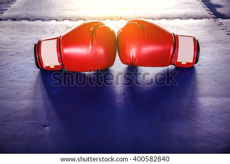Red boxing gloves On Blue rubber flooring - stock photo