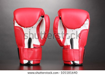 Red boxing gloves on grey background - stock photo