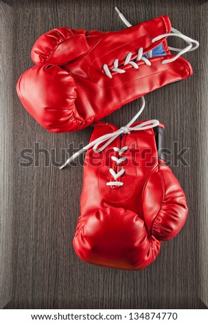 Red boxing gloves over wooden dark background - stock photo