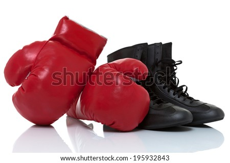Red boxing gloves up agains each other and shoes isolated on white