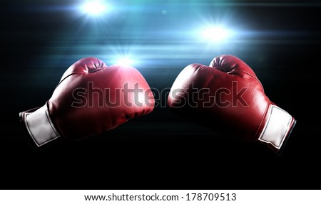 Red boxing gloves with the glow of flashes in the background.