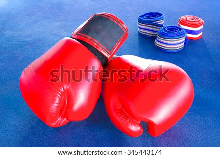 Red boxing gloves with three rolls of hand bandage on blue exercise mat. - stock photo