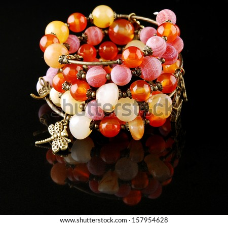 Red bracelet on black background - stock photo