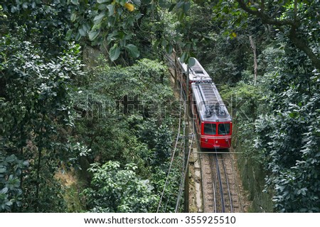 Red Brazilian train traveling through thick green jungle at Tijuca National Forest in Rio de Janeiro Brazil