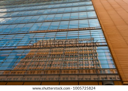 Red Brick High Rise Reflected In Glassed Side Of Modern Office Building