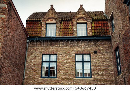 Red brick house facade with windows in Bruges, Belgium