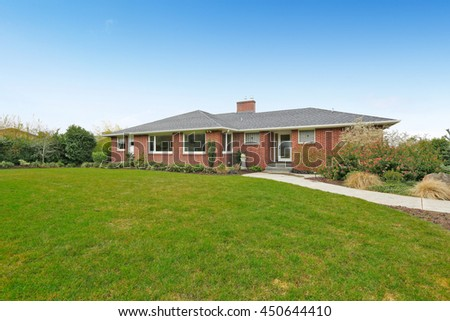 Red brick house with tile roof. General front view. Large green lawn. - stock photo