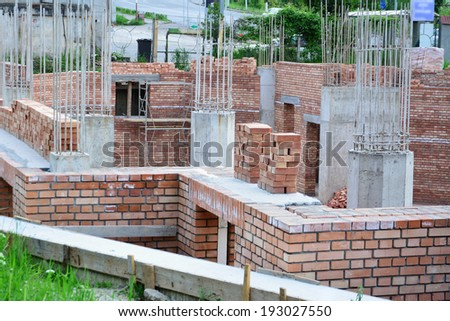 Red brick masonry and reinforced concrete pillars on house under construction. - stock photo